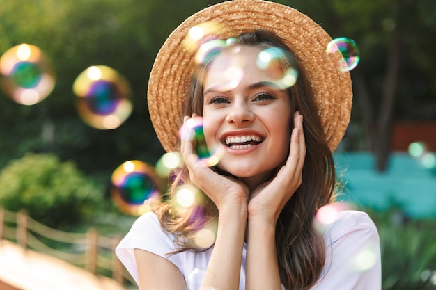 Cheerful young girl blowing soap bubbles at the park outdoors