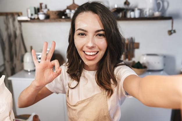 Веселая молодая девушка, покрытая мукой, делает селфи на кухне