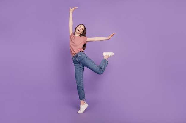 紫の背景で隔離の陽気な若い女の子のダンス