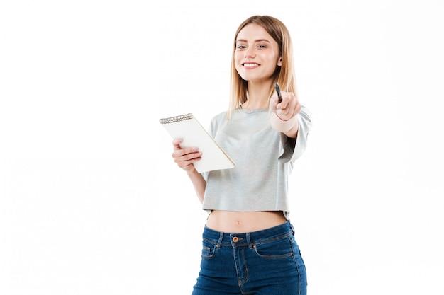 Жизнерадостная маленькая девочка держа блокнот и указывая ручка на фронт