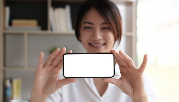 Cheerful young girl holding smartphone on hand with a blank screen.