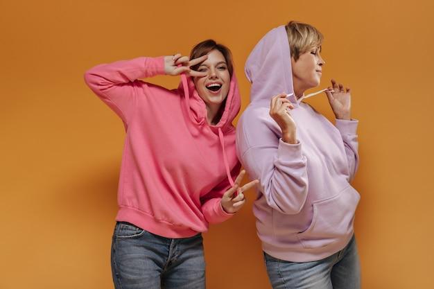 ピースサインを示しているピンクのスウェットシャツの陽気な若い女の子、オレンジ色の背景にライラックのクールなパーカーで現代の女性とウィンクとポーズ。