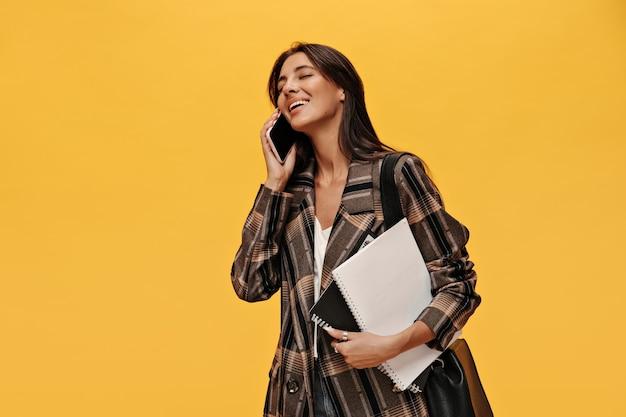 スタイリッシュな特大のジャケットの陽気な若い女の子が電話で話します