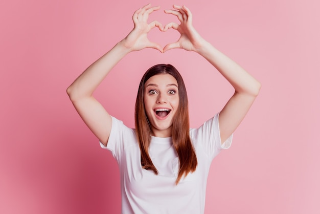 Cheerful young girl is gesturing a heart with fingers raise hands amazed face