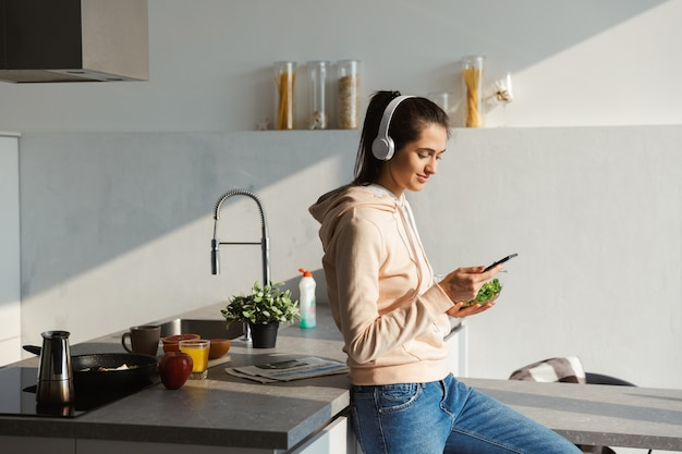 Cheerful young girl listening to music with headphones at the kitchen at home, eating salad from a bowl