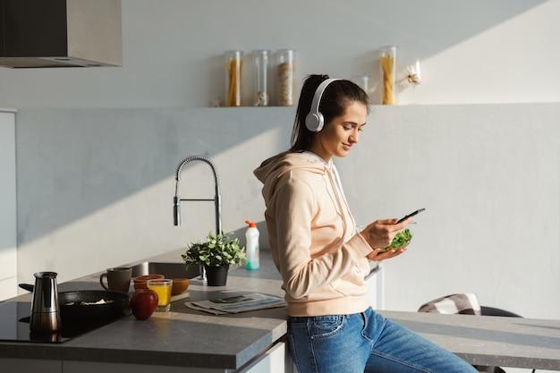 Веселая молодая девушка слушает музыку в наушниках на кухне дома, ест салат из миски