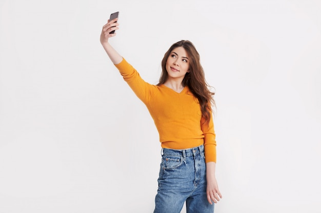 A cheerful young girl in an orange sweater takes a selfie photo on her phone. stylish brunette on a light background with space for text