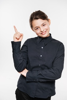 Cheerful young girl posing and pointing