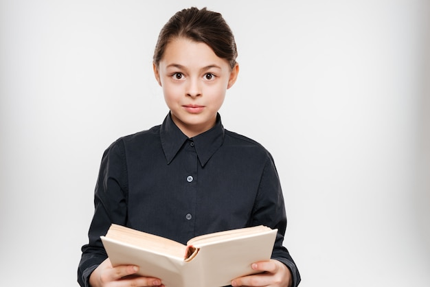 Cheerful young girl reading book
