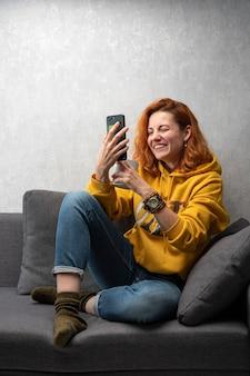 쾌활한 어린 소녀가 소파에 앉아 이야기를 촬영합니다. 화상 통화 채팅.