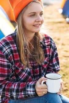 야외 캠프장에 앉아 컵을 들고 명랑 소녀