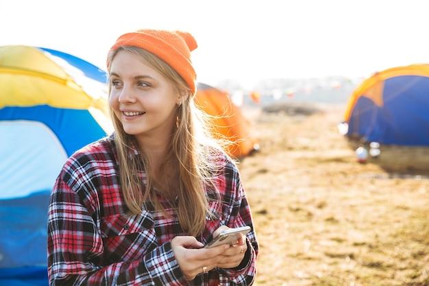 휴대 전화를 사용하여 야외 캠프장에 앉아 명랑 소녀