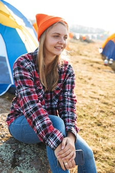 Cheerful young girl sitting at the campsite outdoors, using mobile phone