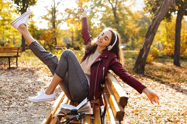 Веселая молодая девушка сидит на скамейке в парке, слушает музыку в наушниках