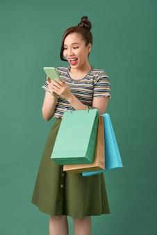 緑の上に立って、買い物袋を持って、携帯電話を使用して陽気な少女