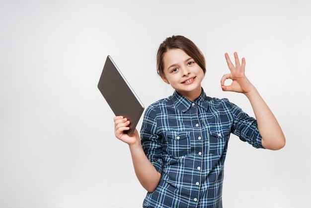 タブレットコンピューターを使用して陽気な若い女の子は大丈夫ジェスチャーを作る