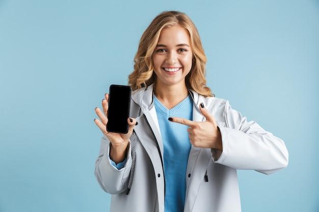 Веселая молодая девушка в плаще стоит изолированно, указывая пальцем на пустой экран мобильного телефона