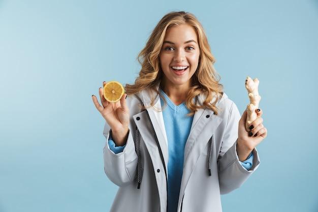 레몬과 생강을 보여주는 절연 서 비옷을 입고 쾌활 한 어린 소녀