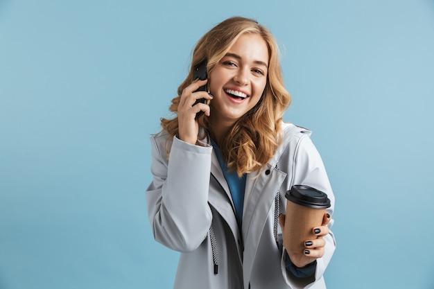 孤立して立って、携帯電話で話し、コーヒーカップを保持しているレインコートを着ている陽気な少女