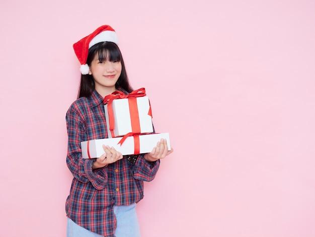 Веселая молодая девушка в шляпе санта-клауса с подарочными коробками на розовом фоне