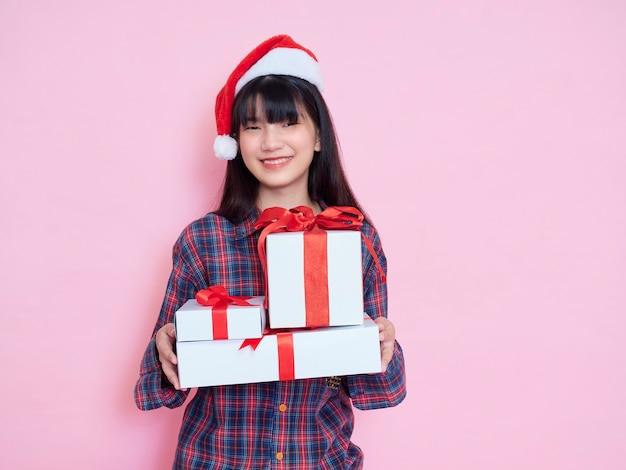 ピンクのギフトボックスを保持しているサンタの帽子をかぶって陽気な若い女の子