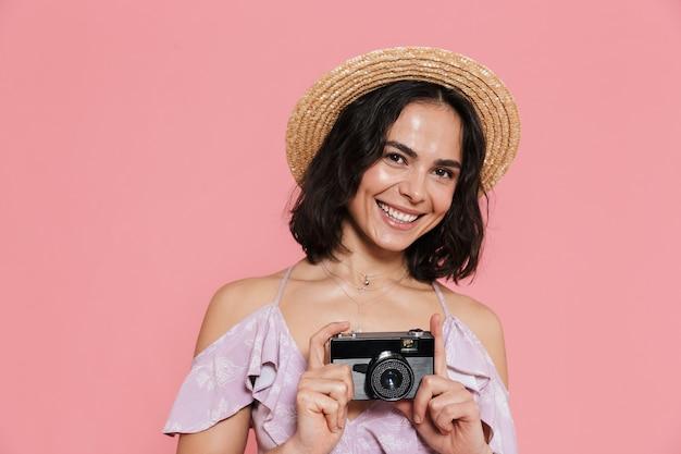ピンクの壁に孤立して立っている夏のドレスを着て、写真カメラで写真を撮る陽気な少女