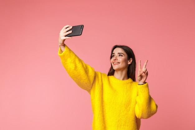 ピンクの上に孤立して立っているセーターを着て、自分撮りをしている陽気な少女