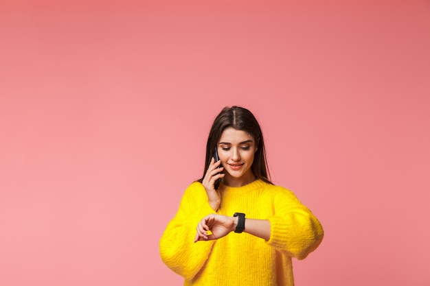 쾌활한 어린 소녀 입고 스웨터 핑크 이상 격리 서, 휴대 전화 통화, 시간 확인