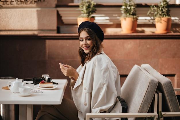 검은 머리, 베레모, 클래식 베이지색 트렌치 코트를 입은 쾌활한 어린 소녀가 도시 카페 테라스 테이블에 앉아 웃고, 아침 식사로 치즈케이크와 차를 먹고 있습니다.