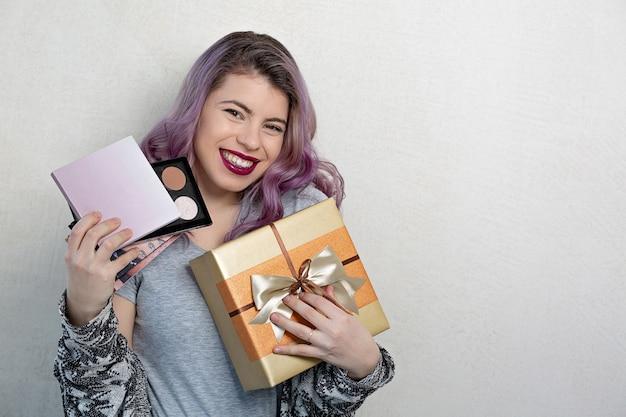 化粧品とギフトボックスを保持している紫色の髪の陽気な少女。テキスト用のスペース