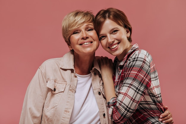 カメラを見て、ピンクの背景にベージュのジャケットのブロンドの女性と一緒に微笑んでいる格子縞のシャツの短い髪型の陽気な若い女の子。