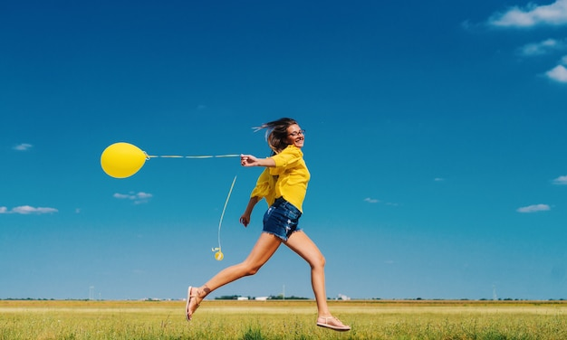 Cheerful young girl in yellow shirt running in field with yellow balloon in her hand.