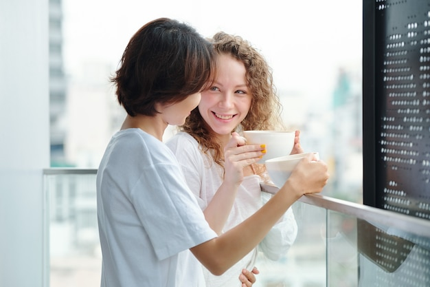Cheerful young girlfriends in love standing on balcony, drinking morning coffee and looking at each other