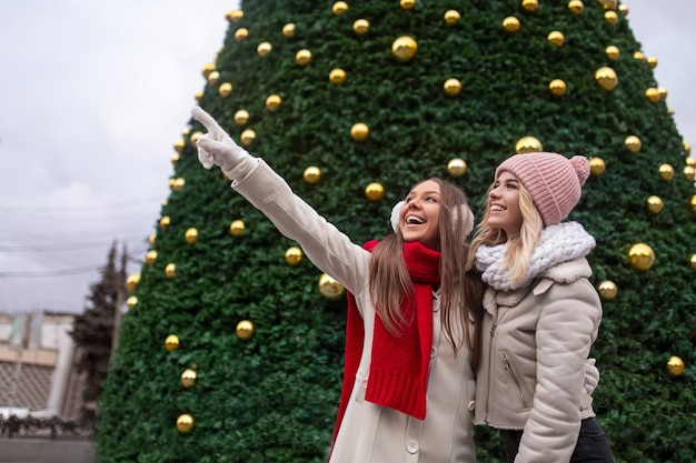 Cheerful young girlfriends in warm winter clothes looking away with excitement while standing together near decorated green christmas tree on urban square