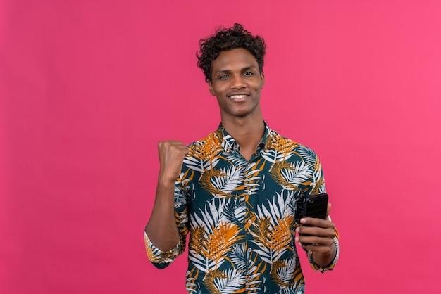 スマートフォンを握りしめている握りこぶしで葉を印刷したシャツに葉の巻き毛のある陽気な若いハンサムな浅黒い肌の男