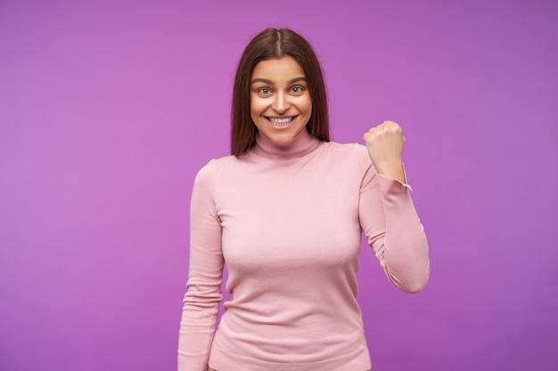 보라색 벽 위에 서있는 동안 분홍색 폴로 넥 옷을 입고 기꺼이 그녀의 주먹을 올리고 넓게 웃고 느슨한 머리카락을 가진 쾌활한 젊은 녹색 갈색 머리 여자