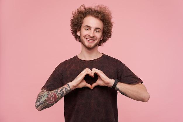 Allegro giovane maschio dagli occhi verdi ricci tatuato cuore pieghevole con le mani alzate e guardando la telecamera con un sorriso affascinante, in posa sopra il muro rosa