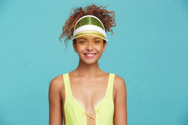 파란색 배경 위에 절연 카메라를 긍정적으로 보면서 undelip을 물고 즐겁게 웃는 곱슬 머리를 가진 쾌활한 젊은 녹색 눈의 빨간 머리 여성