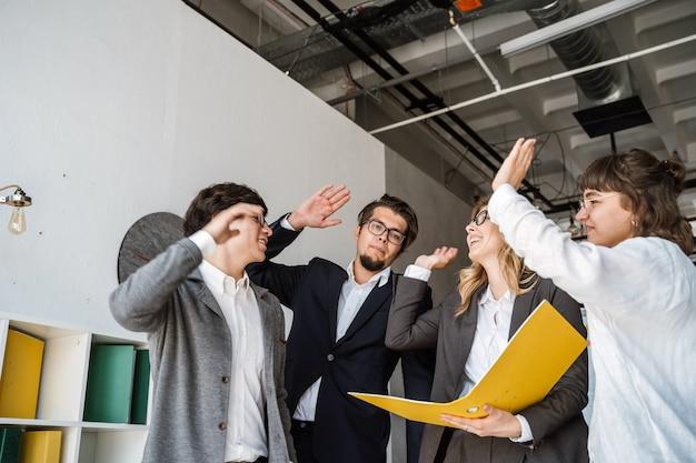 オフィスに立って、ハイタッチを与える人々の陽気な若いグループ