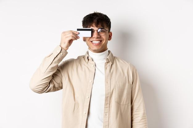 本物の笑顔と白い背景に幸せに立っているプラスチックのクレジットカードを示す陽気な若い男...