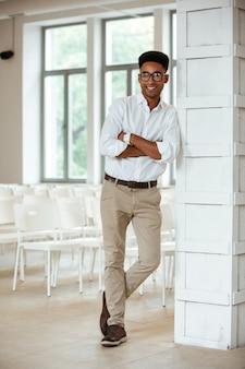 陽気な若いハンサムなアフリカ人が事務所に立っています。