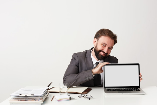 Cheerful young handsome bearded businessman with short brown hair wearing grey suit while sitting at working table over white wall, showing screen of his laptop and smiling broadly