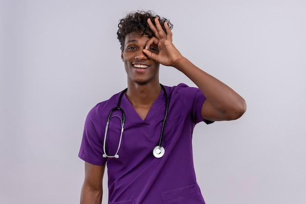 A cheerful young handsome dark-skinned doctor with curly hair wearing violet uniform with stethoscope peeking through a hole formed with his thumb and index finger