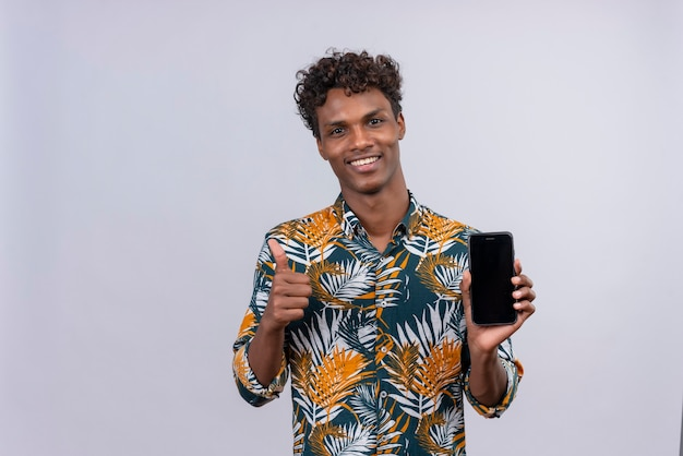 Cheerful young handsome dark-skinned man with curly hair in leaves printed shirt showing a blank smart phone screen with thumbs up