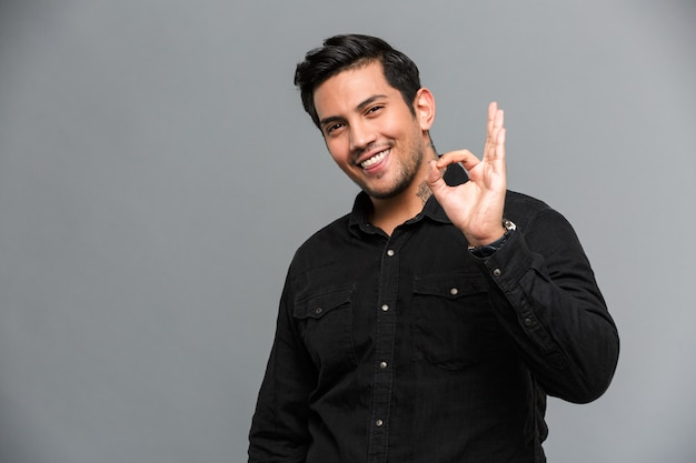 Cheerful young handsome man showing okay gesture.