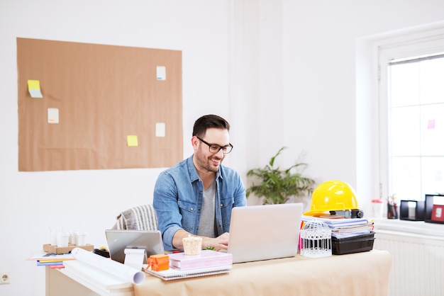 Cheerful young handsome modern director working on a laptop in his large bright office.