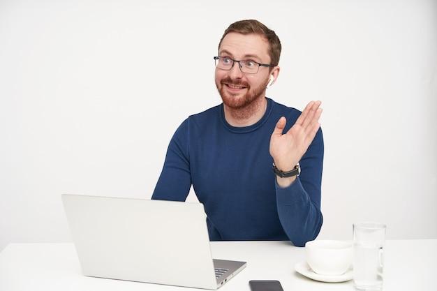 陽気な若いハンサムな剃っていない金髪の男は、ラップトップで白い背景の上にテーブルに座って、こんにちはジェスチャーで手を上げながら喜んで笑っています