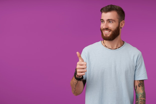 Cheerful young handsome unshaved male with tattooes looking aside with sincere wide smile and showing raised thumb, wearing blue t-shirt while posing on purple