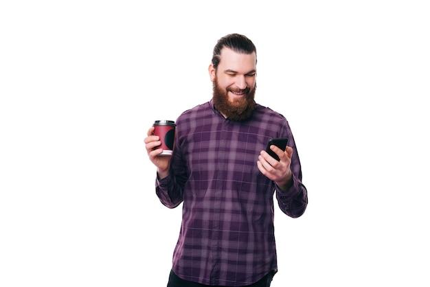 Веселый молодой счастливый бородатый мужчина держит чашку кофе и использует смартфон