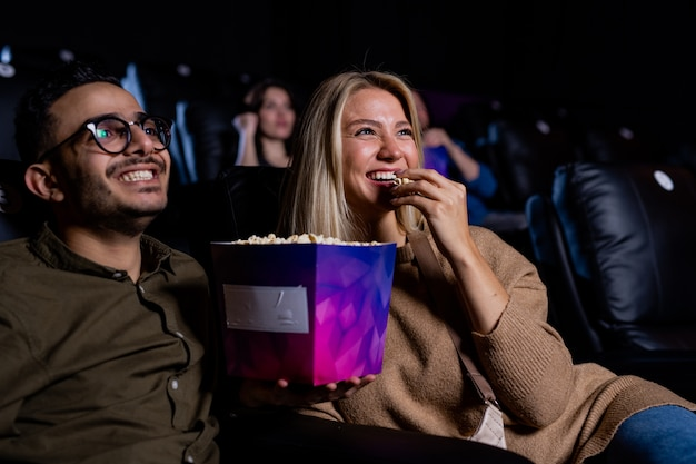 Cheerful young heterosexual couple eating popcorn while watching funny comedy in cinema at leisure